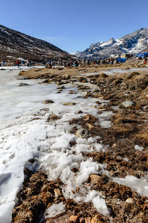 Four wheel drive cars parking area with frozen pond, snow, tourists and market with Yunthang Valley in the background in winter in Zero Point at Lachung. North Sikkim, India. Editorial