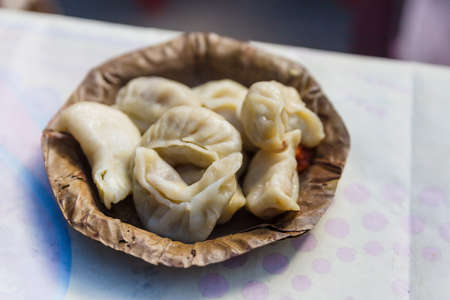 Momos served in dry leaves plate in village market in winter at Gangtok, Sikkim. India. Stock Photo