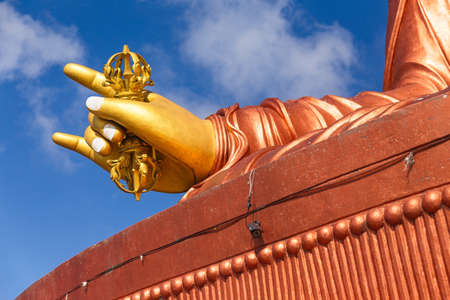 Close up at the right golden hand with mace of Guru Rinpoche statue, the patron saint of Sikkim in Guru Rinpoche Temple at Namchi. Sikkim, India. Stock Photo