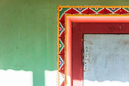Tibetan decoration wall with green, red and yellow color with sunlight of Guru Rinpoche Temple at Namchi. Sikkim, India.
