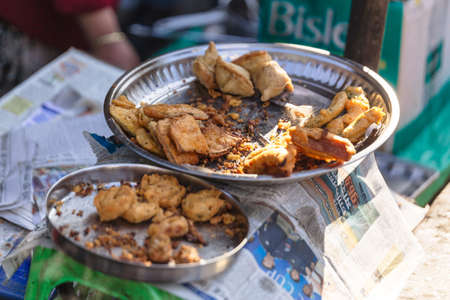 passerby: Close-up fried banana on steel plate in the market near Tiger Hill in winter at Darjeeling, India. Stock Photo