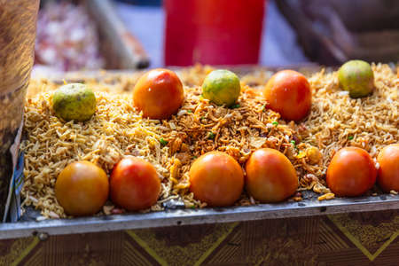 sev: Sev with tomato and lime is a popular Indian snack food consisting of small pieces of crunchy noodles made from chickpea flour paste at street local market in Darjeeling. India.