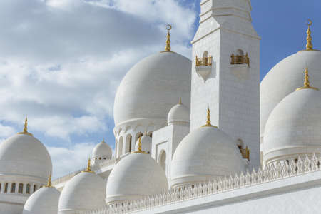 Close-up marble domes with golden pillar with Islamic sign on the top of Sheikh Zayed Grand Mosque with blue sky in the morning at Abu Dhabi, UAE.
