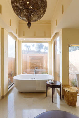 Modern bathroom area with bath tub and sofa inside in the morning at Abu Dhabi, UAE. Stock Photo