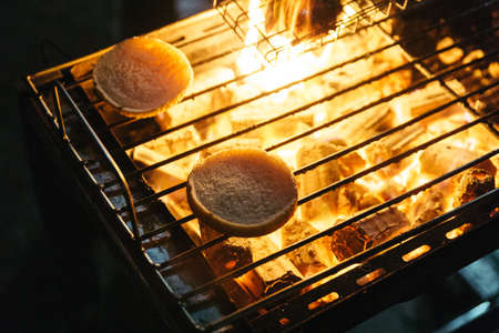 ablaze: Burger buns grill with burning charcoal with fire on the stove with grill on top in Bangkok, Thailand.