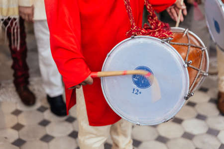 Close-up Indian musician guy drumming Dhol and wearing red Bandhgala at Indian wedding ceremony in Bangkok, Thailand.