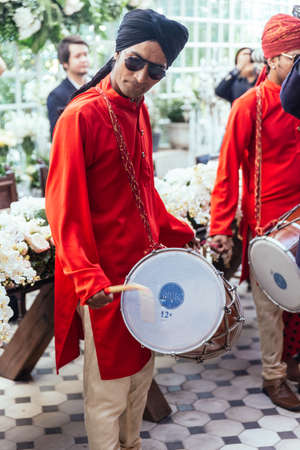 Indian musician guy drumming Dhol and wearing red Bandhgala and black Pheta at Indian wedding ceremony in Bangkok, Thailand.