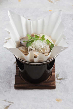 cilantro: Japanese Clam Soup with Clear Broth (Asari no ushiojiru) with sliced Japanese scallion and coriander served in hot paper bowl on washi (Japanese paper).