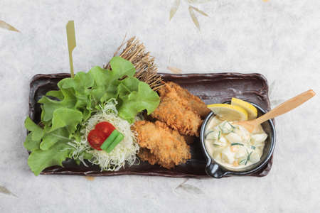 Top view of Japanese tempura mussel is deep fried mussel mixing with flour served with egg salad with sliced cucumber and lemon, sliced cabbage, tomato and green oak in black long plate on washi.