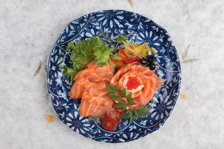 Top view of Salmon sashimi served with lime sauce, potato salad and ikura served in panted ink plate on washi (Japanese paper). Stock Photo