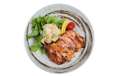 Isolated Top view of Teriyaki chicken served with potato salad, sliced lemon, totmato and green oak in round stone plate.