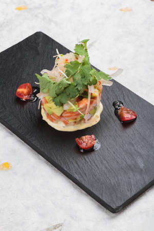 Diced salmon salad with avocado, tomato, onion, chilli, and coriander served in black rectangle stone plate on washi (Japanese paper).