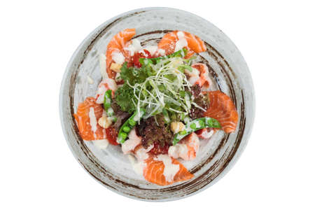 Isolated top view of Salmon and shrimp salad with red oak, pea, crouton with mayonnaise topping with wild rocket in ink painted ceramic bowl.