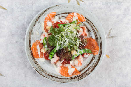 Top view of Salmon and shrimp salad with red oak, pea, crouton with mayonnaise topping with wild rocket in ink painted ceramic bow on washi (Japanese paper). Stock Photo