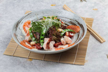 Salmon and shrimp salad with red oak, pea, crouton with mayonnaise topping with wild rocket in ink painted ceramic bowl with chopstick on makisu (meal mat).