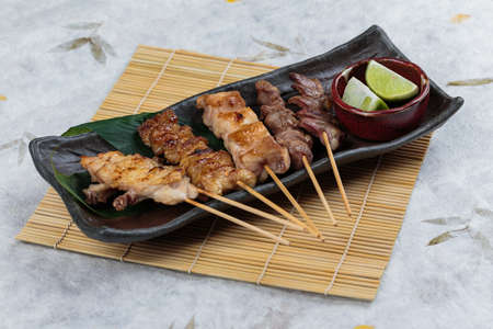 Yakitori (Japanese-Style Grilled Chicken Skewers) with chicken and internal organ served with sliced lime on black stone plate on makisu (Meal mat). 版權商用圖片