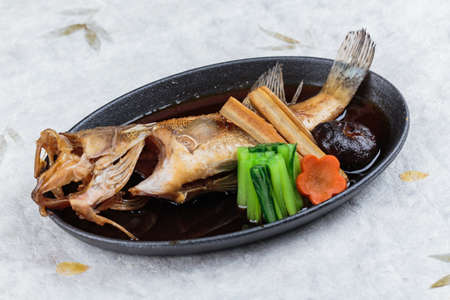 Fried snapper with radish, carrot, shiitake and choy sum in hot plate on washi (Japanese paper).