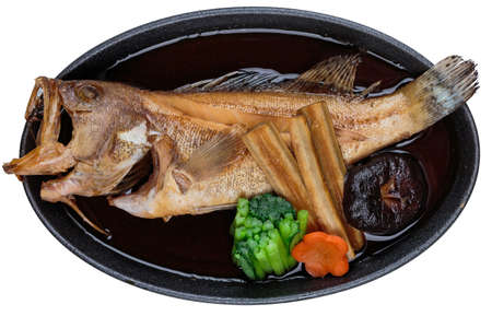Isolated top view of Fried snapper with radish, carrot, shiitake and choy sum in hot plate on wooden plate.