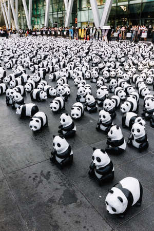 Many panda sculptures place on the floor is an art exhibition with audiences and visitors take photos in Bangkok, Thailand.