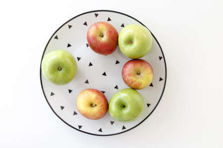 Top view of Red and green apples in white plate with black triangles pattern on white background.