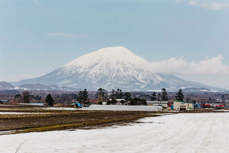 Close up Mount Yotei (inactive stratovolcano) with village and snow cover on the ground in winter in Hokkaido, Japan.