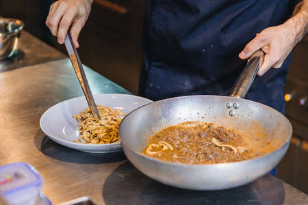 Chef plating cooked Wagyu Ragu with Tagliatelle pasta in white plate.