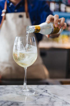 Bartender gently pour alcohol and soda in a wine glass with ice for making cocktail. Stock Photo