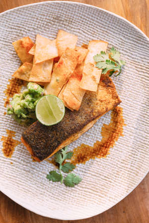 Grilled well done salmon steak served with pistachio sauce and sliced lime topping with fried sticks.