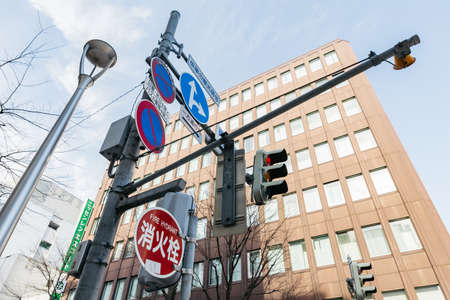 Road traffic light and sign with buildings in the background at Sapporo in Hokkaido, Japan. Editorial
