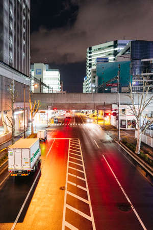 Empty Sapporo street with orange and red lights reflection in the night at Hokkaido, Japan.