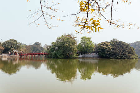 Red Bridge at Hoan Kiem Lake with tress and reflected shadow and branches in foreground in Hanoi, Vietnam. Editorial