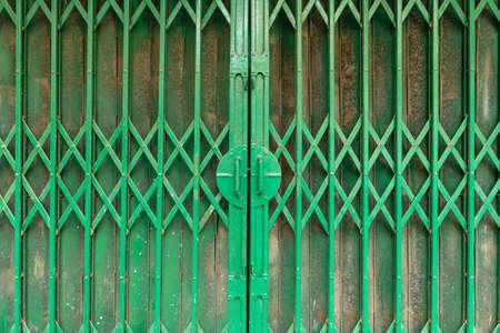 Close up old green steel sliding door of retail in Hanoi, Vietnam. Stock Photo
