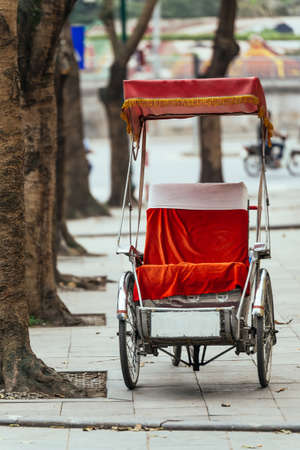 Empty tricycle with red seat stop on the foot path under the tree in Hanoi, Vietnam.