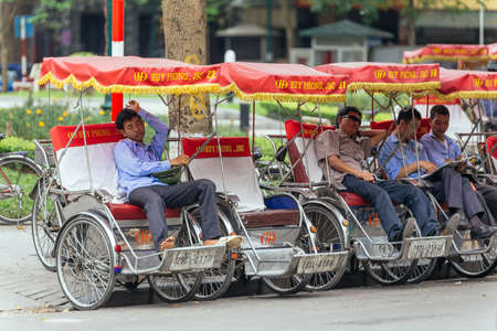 Tricycles with drivers waiting for service on the street in Hanoi, Vietnam.