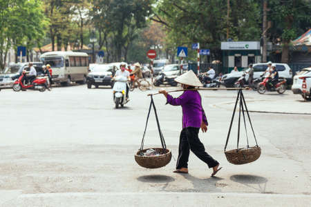 Woman wearing purple cloth and conical hat. Carry baskets with stuff inside with a carrying pole on the street in Hanoi, Vietnam.