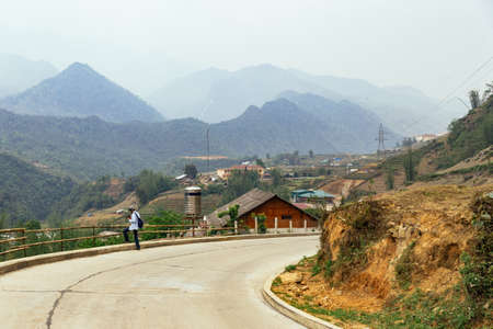 Tourist walking on main road with villages and mountain in the background in summer in the morning in Sa Pa, Vietnam.