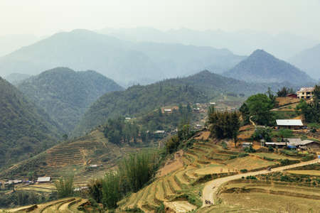 Step ladder farm on the hill with villages and mountain in the background in summer in the morning in Sa Pa, Vietnam.