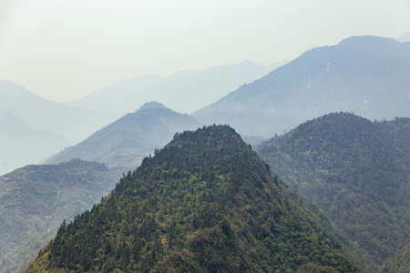 Green mountain with fog and mountain layer in the background in summer in the morning in Sa Pa, Vietnam.