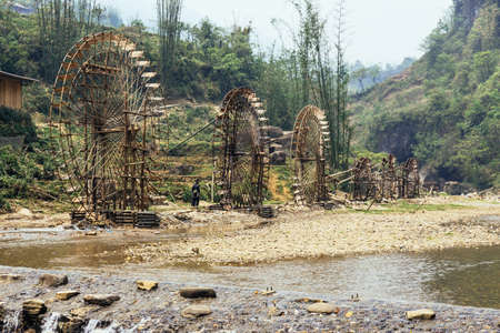 Elaborate water wheels made from bamboo with trees in the background in summer at Cat Cat Village in Sa Pa, Vietnam. Stock Photo
