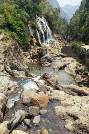 Waterfall with river flow with rocks at Cat Cat Village in summer in Sa Pa, Vietnam.