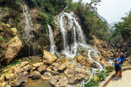 Couple tourists looking Waterfall with river flow with rocks in summer at Cat Cat Village in summer in Sa Pa, Vietnam.
