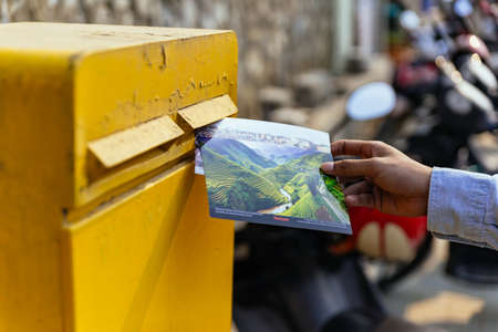 Man right hand sending postcard in yellow post box in summer in Sa Pa, Vietnam.