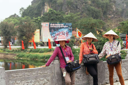 Women photographers wearing conical hat waiting for tourists to take a photo near Trang An with mountain in the background in summer in Ninh Binh, Vietnam.