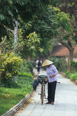 Vietnamese woman wearing conical hat walking with her bicycle on the way in summer near Trang An Grottoes in Ninh Binh, Vietnam.