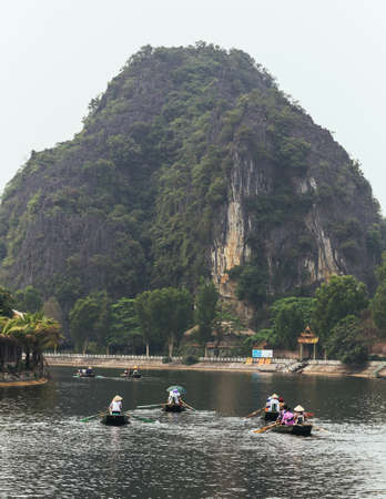 Landscape of mountain and river with tourist on moving boats in summer at Trang An Grottoes in Ninh Binh, Vietnam.