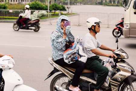 Woman take a while sitting on moving motorcycle on the street of Hanoi, Vietnam.