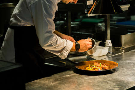 Chef plating dish on kitchen counter while recording at kitchen hotel.