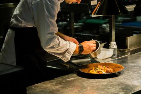 Chef-kok schotel op aanrecht tijdens het opnemen in keukenhotel. Stockfoto