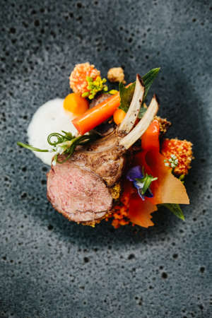 Modern French cuisine: Close up roasted Lamb neck & rack served with carrot, yellow curry served in black stone plate. Фото со стока