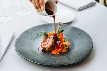 Modern French cuisine: Roasted Lamb neck & rack served with carrot, yellow curry and lamb sauce. Served in black stone plate with fork and knife. Zdjęcie Seryjne - 101050997